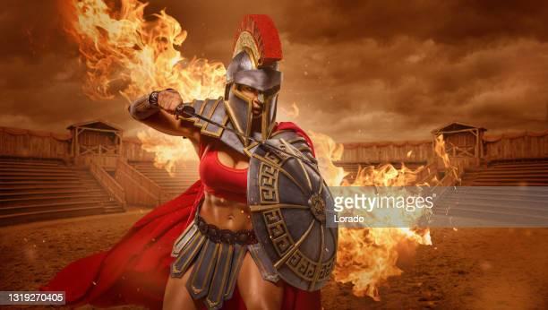 un gladiateur de guerrier féminin retenant une arme dans une arène - actrice photos et images de collection