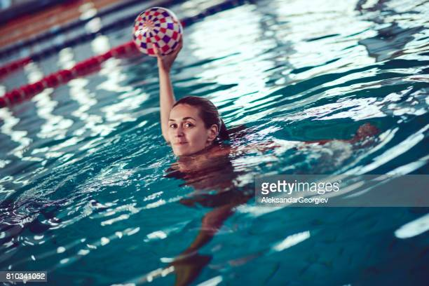 Female Water Polo Player Aiming at Indoor Swimming Pool