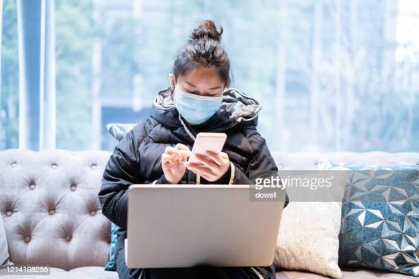 female  wearing face mask while working on laptop - lockdown - fotografias e filmes do acervo
