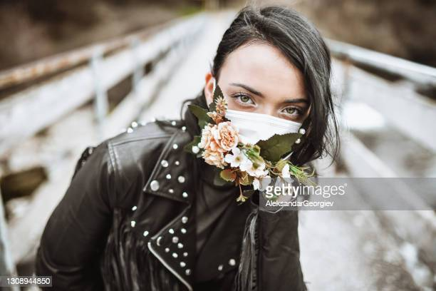 female wearing flowery face mask and leather clothing - punk music stock pictures, royalty-free photos & images