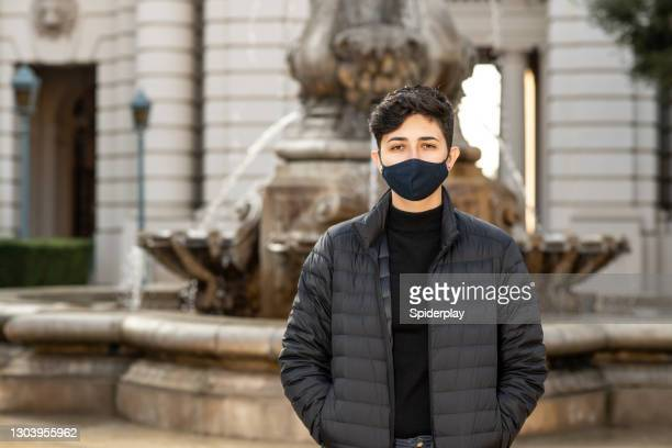 female wearing mask in front of a fountain - pasadena california stock pictures, royalty-free photos & images