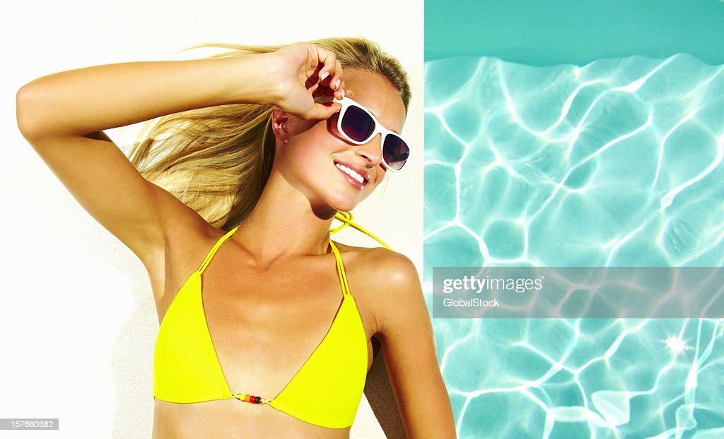 Femme porte des lunettes de soleil et un bikini, allongé au bord de la piscine