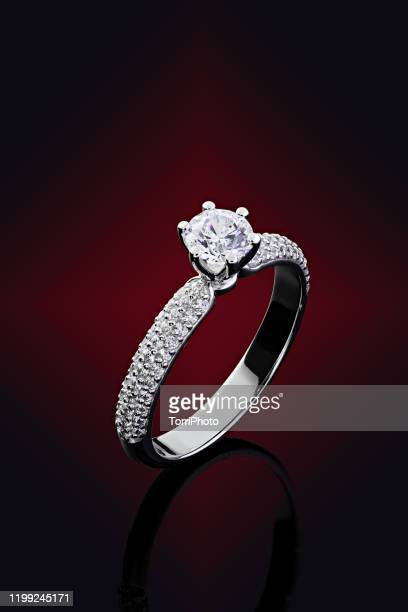 female wedding proposal diamonds ring on red and black background - white gold stock pictures, royalty-free photos & images