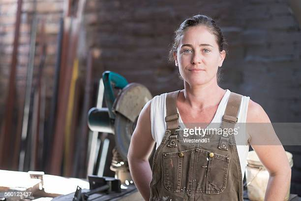 Female welder in metal workshop, portrait