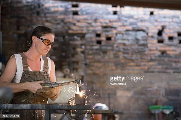 Female welder working in metal workshop
