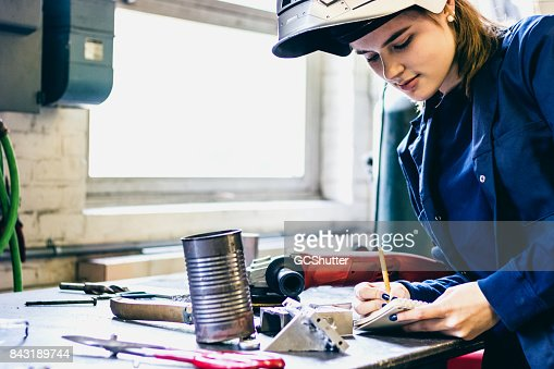 Female welder writing notes down for her process