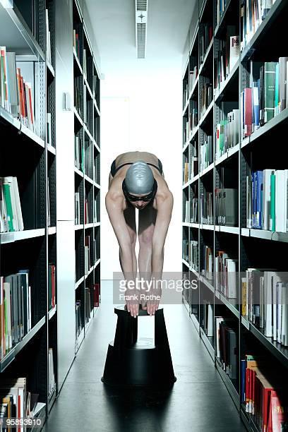 female wet swimmer in a library beside books