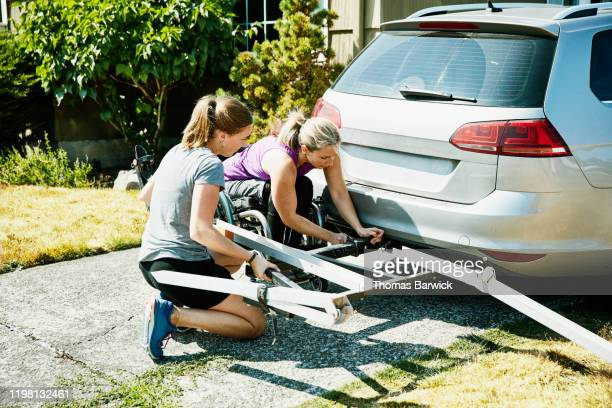 female wheelchair athlete and assistant attaching bike rack to back of car - disabilitycollection stock pictures, royalty-free photos & images