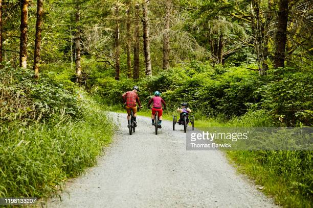 female wheelchair athlete and friends on mountain bike ride - forward athlete stock pictures, royalty-free photos & images
