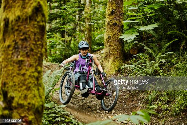 female wheelchair athlete descending trail on adaptive mountain bike - differing abilities fotografías e imágenes de stock