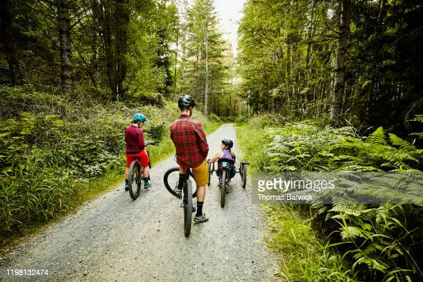 female wheelchair athlete in discussion with friends while resting during ride up trail on mountain bike - forward athlete stock pictures, royalty-free photos & images