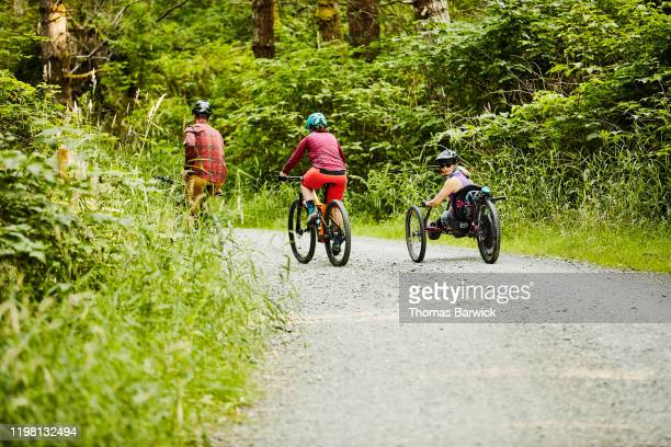 female wheelchair athlete on mountain bike ride with friends - forward athlete stock pictures, royalty-free photos & images