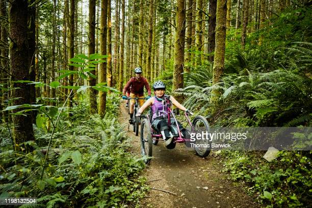 female wheelchair athlete riding adaptive mountain bike on trail with friend - forward athlete stock pictures, royalty-free photos & images