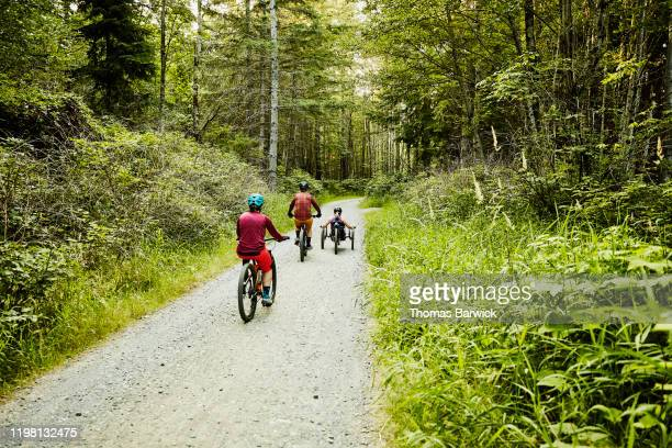 female wheelchair athlete riding adaptive mountain bike up trail with friends - forward athlete stock pictures, royalty-free photos & images