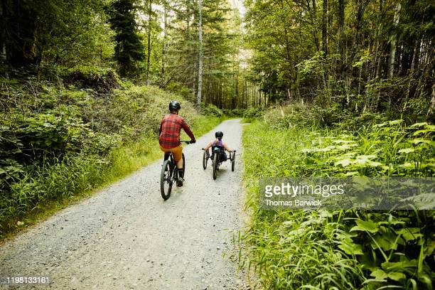 female wheelchair athlete riding adaptive mountain bike up trail with friend - forward athlete stock pictures, royalty-free photos & images