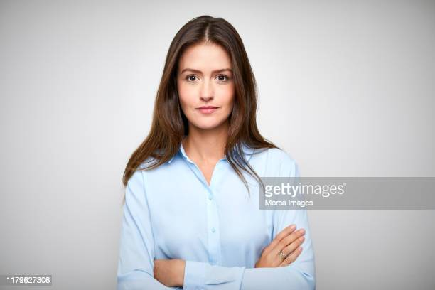 female white collar worker with arms crossed - in den dreißigern stock-fotos und bilder