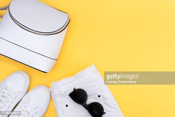 female white sneakers and jeans on yellow background with copy space. top view. summer fashion, shopping, capsule wardrobe concept. creative flat lay. modern and casual outfit - fashion collection stock pictures, royalty-free photos & images