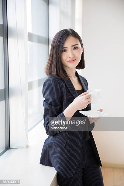 female white-collar drink coffee