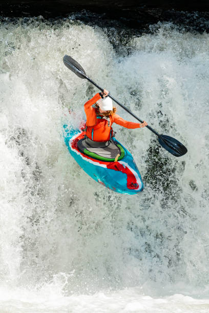 Female Whitewater Kayaker Dropping Over a Waterfall
