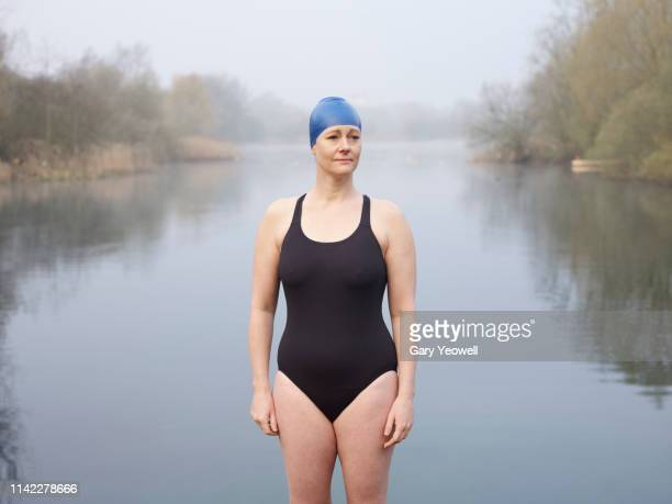 female wild swimmer standing by a lake - achievement stock pictures, royalty-free photos & images
