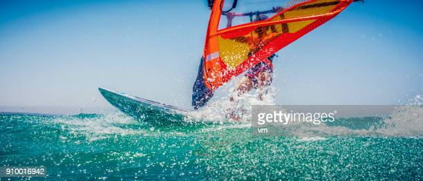 female windsurfer making a splash - windsurfing stock pictures, royalty-free photos & images