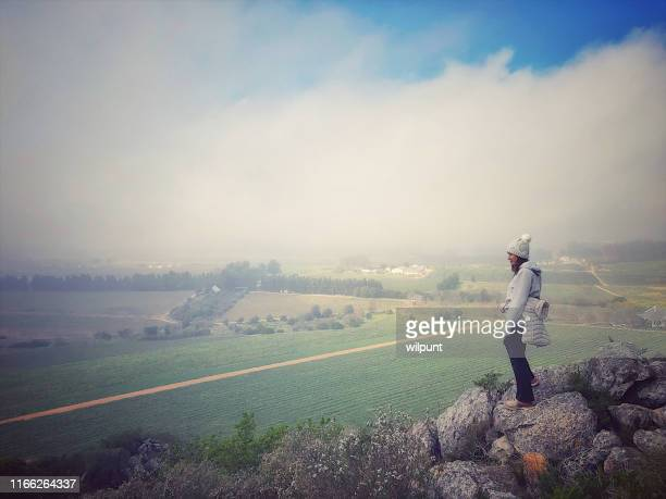 female winemaker looking down from a rocky outcrop towards resting vineyard in winter - western cape province stock pictures, royalty-free photos & images