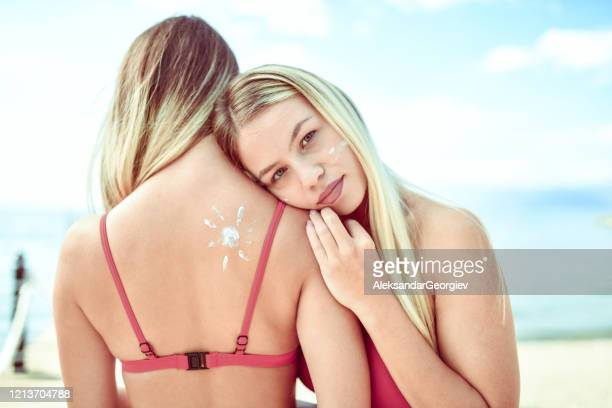 female with a sunscreen sun drawing on her back embraced by her cute friend - sexy drawing stock pictures, royalty-free photos & images