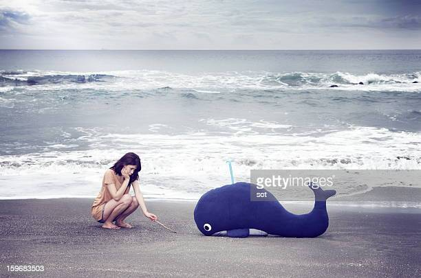 Female with a whale in the beach