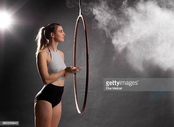 female with aerial hoop looking at white dust like cloud