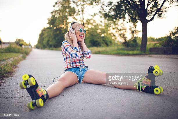 female with headphones - roller skating stock photos and pictures