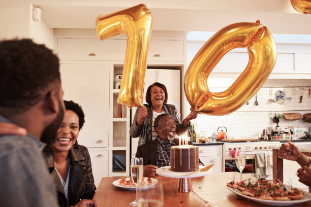 female with number 70 balloons at birthday party - best friend birthday cake stock pictures, royalty-free photos & images