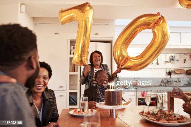 female with number 70 balloons at birthday party - disruptagingcollection stock pictures, royalty-free photos & images