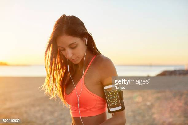 female with phone attached to arm band at beach - armband stock pictures, royalty-free photos & images