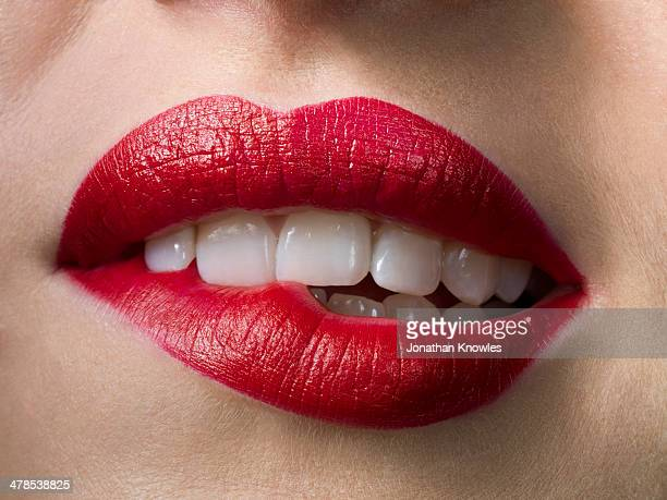 female with red lipstick, biting lips, close up - menselijke lippen stockfoto's en -beelden