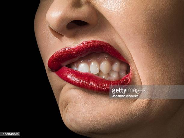 Female with red lipstick, grimacing, close up