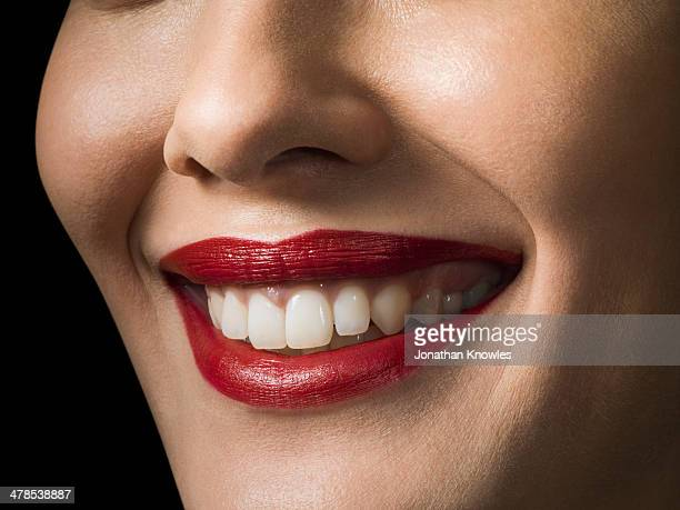 Female with red lipstick smiling, close up