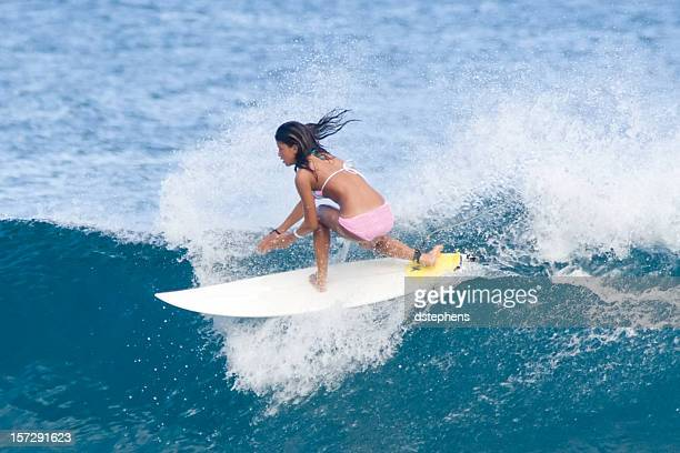 Female with tanned skin surfing a wave
