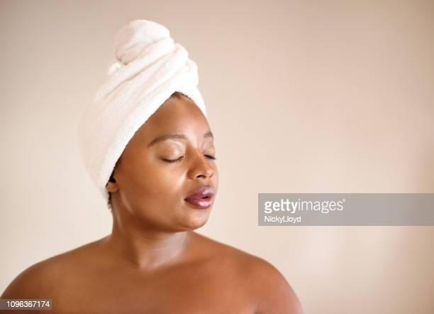 female with towel wrapped on her head against brown background. - wrapped in a towel stock pictures, royalty-free photos & images
