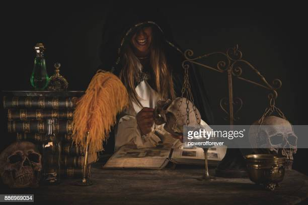 Female Wizard at table with Magical Items
