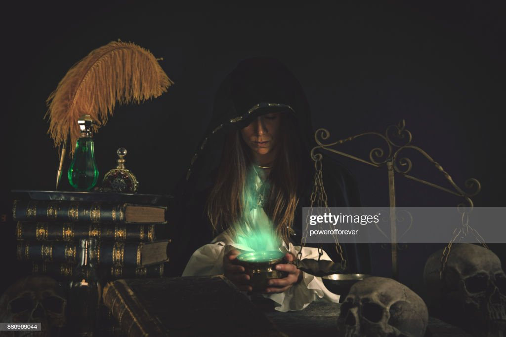 Female Wizard at table with Magical Items : Stock Photo