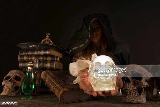Female Wizard holding crystal skull at table with Magical Items
