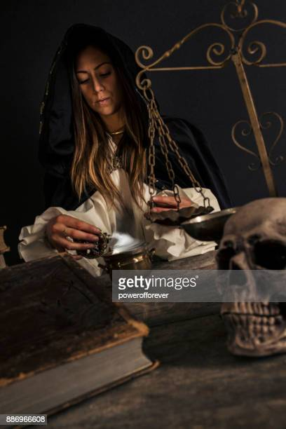 Female Wizard mixing potion at table with Magical Items