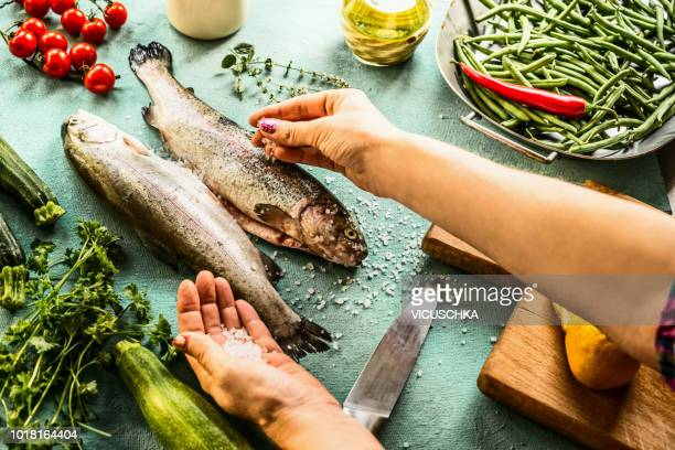 female woman hands sprinkle with salt raw trout fishes - trout stock pictures, royalty-free photos & images