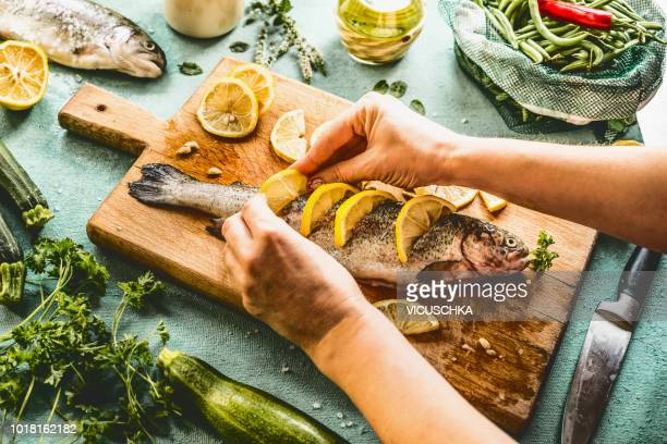 female woman hands  stuff with lemon raw trout fishes - pescado y mariscos fotografías e imágenes de stock