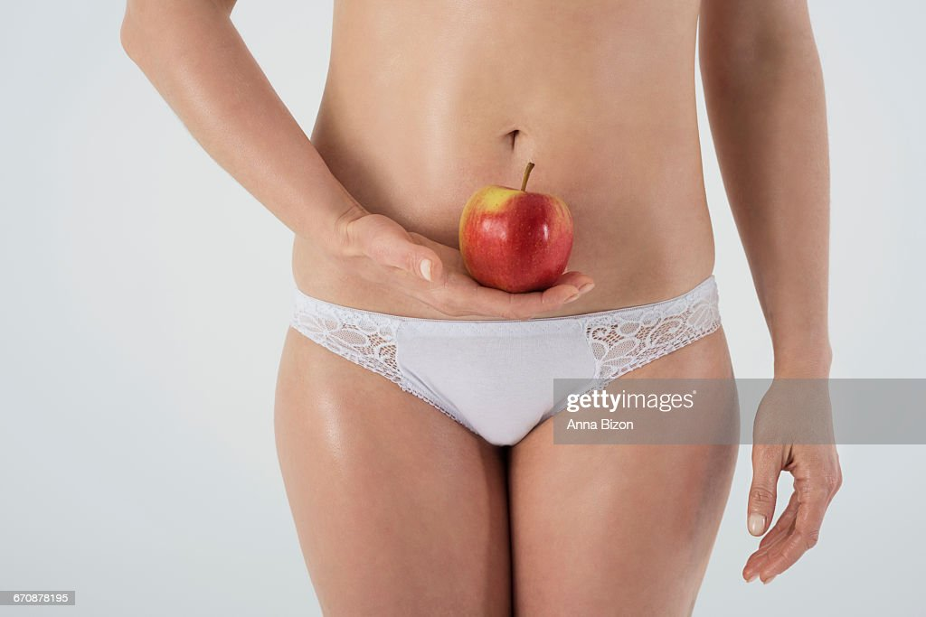 Female womb and an apple. Debica, Poland : Stock Photo