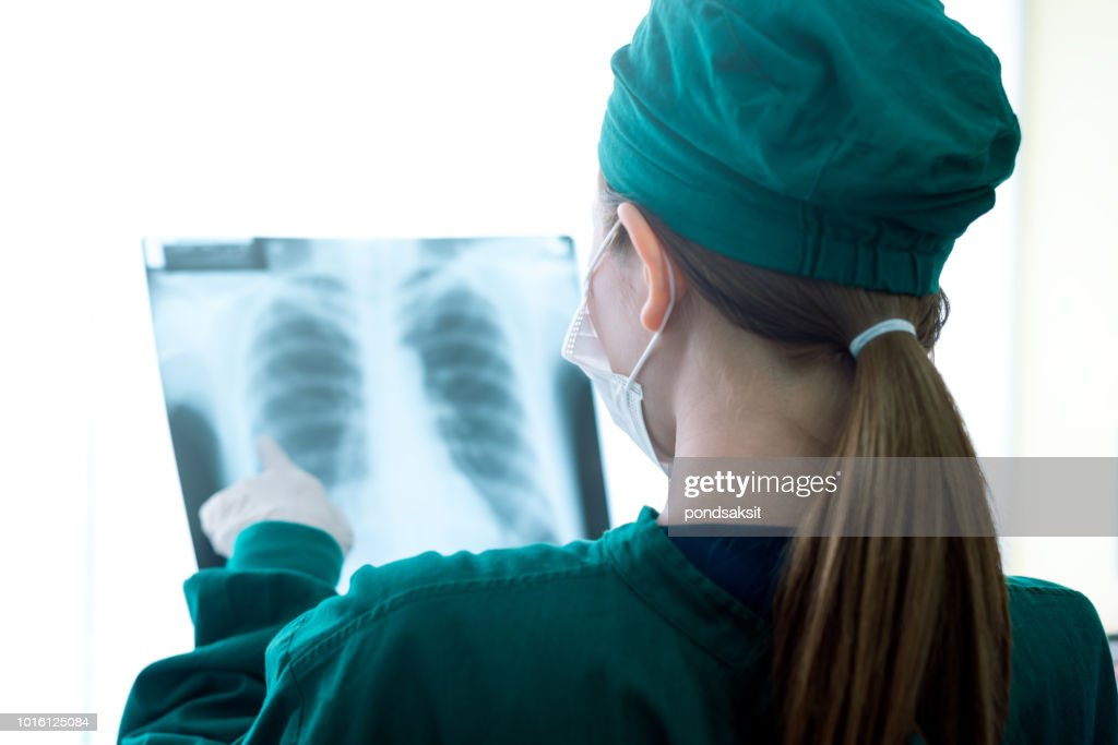 Female women medical doctor looking at x-rays in a hospital : Stock Photo