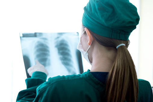 Female women medical doctor looking at x-rays in a hospital 1016125084