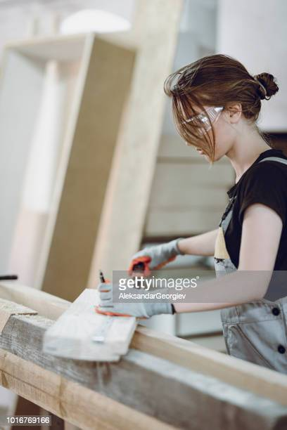 Female Woodwork Technician Measuring Dimensions Of Wooden Plank