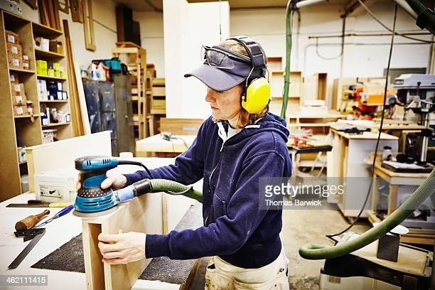 Female woodworker sanding edge of custom cabinet