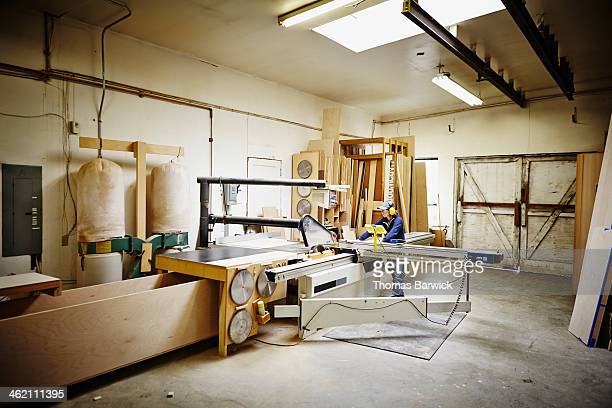 Female woodworker working in woodshop on table saw